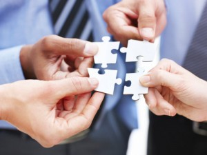 Closeup of businesspeople about to put four puzzle pieces together